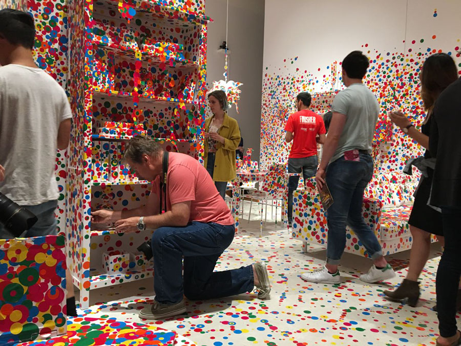 Viewers participating in adding dots to the The Obliteration Room